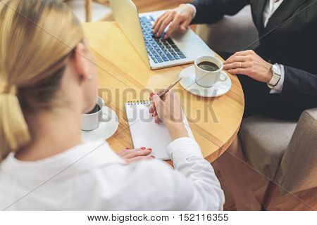 Two businesswomen are working in cooperation. They are sitting at desk and drinking coffee. Lady is typing on laptop. Her colleague is writing with concentration