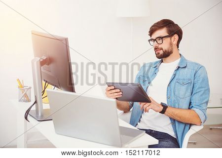 So many devices. Successful handsome young man programming while working in an office and using tablet and other devices.