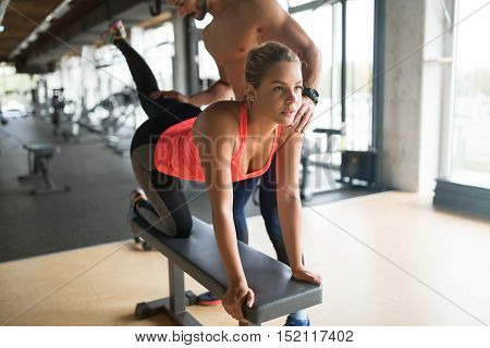Personal trainer helping cute woman in gym