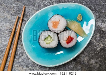 Sushi Hoso maki on plate with chopsticks.