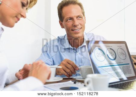 Cheerful colleagues are working together. Middle-aged businessman is drinking coffee and smiling dreamingly. Woman is reading document with concentration