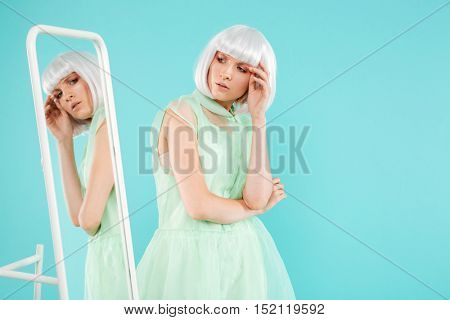 Beautiful young woman in blonde wig standing and posing near the mirror