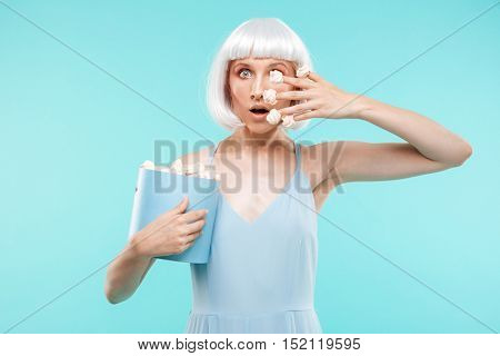 Playful amazed young woman standing and playing with marshmallows on her fingers
