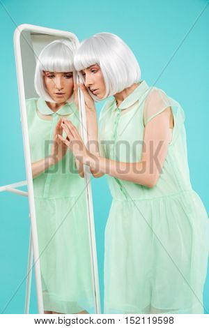 Beautiful young woman in blonde wig standing and touching mirror