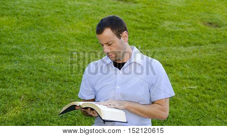 Married man reading with his hand on the Bible.