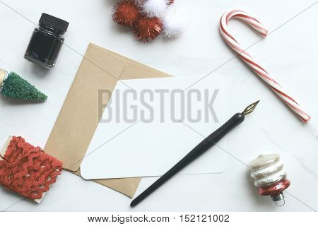 Over head flat lay of a desk top during the Christmas season with letter, pen and ink and Christmas holiday objects