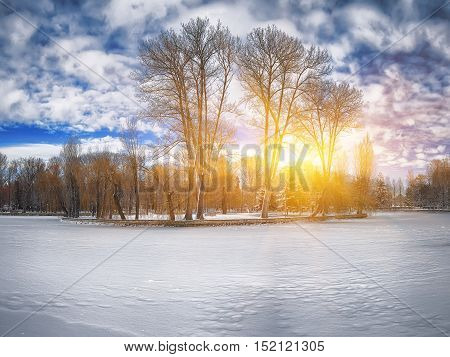 Winter scenery of frozen lake in city park. Blue sky