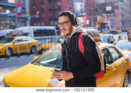 Man walking in New York with headphones and smart phone