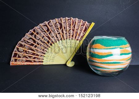 Chinese Fan, Vase With Colored Sand And Spruce Branch On The Dark Background