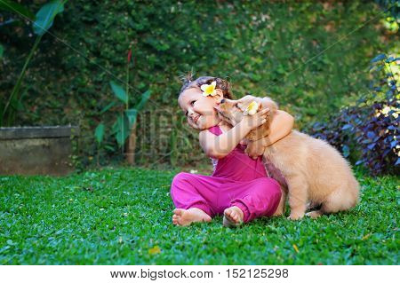 Funny photo of happy baby hugging beautiful golden labrador retriever puppy. Girl play with dog. Family lifestyle positive emotions of children fun games with home pet on summer vacation.