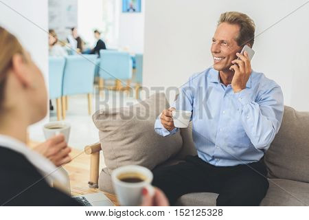 I will call you later. Shot of businessman having informal office meeting while talking on smartphone and drinking coffee