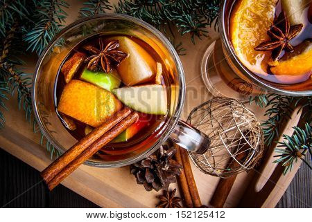 Christmas mulled wine with the addition of fragrant spices, apples, mandarins and oranges, top view, in a tray, on wooden table. With Christmas tree branches and pine cones