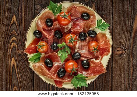Plate with snack - prosciutto jamon ham tomatoes olives and baguette bread top view.