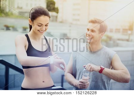 Here we go. Beautiful young athletic girl looking at her smartwatch while handsome man is holding a bottle of water while waiting for training.