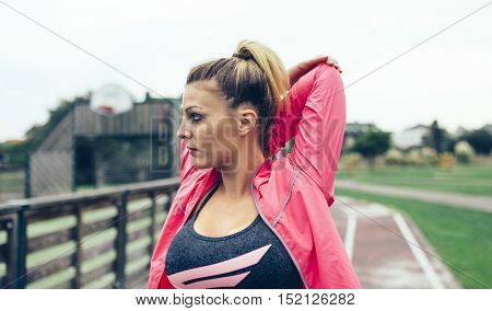 Portrait of young blonde woman with pigtail stretching arms before training outdoors