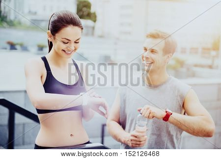 Delighted handsome man and pretty young woman waiting for their training outdoors while using smart watches and wearing sportswear.