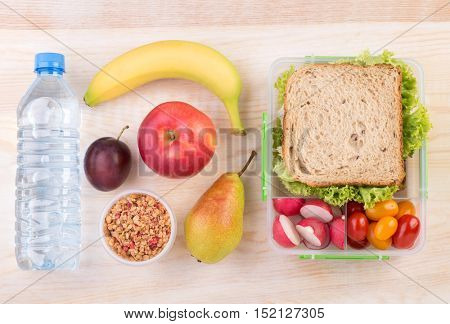 Lunchbox with a sandwich, fruits, vegetables, and water, top view with copy space