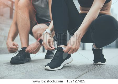 Time to start. Athletic cheerful man and pretty young woman tying shoelaces and preparing for training while waiting near stadium together.