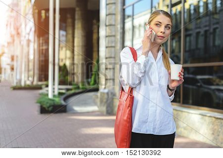Time to stroll. Beautiful girl with red bag walking down street, talking on smartphone and holding coffee in hand