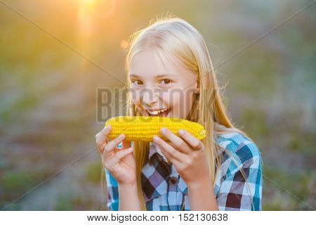 Happy girl eating healthy corn on the cob.
