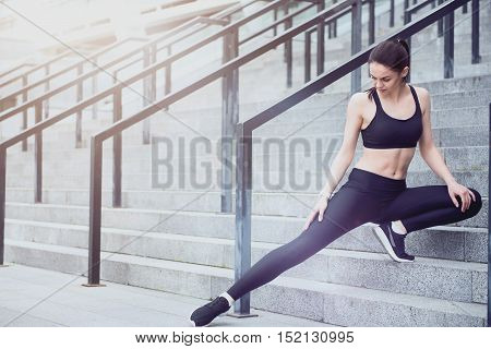 Show your strength. Slim pretty young girl doing sport exercises and warming up while spending time near the stadium.