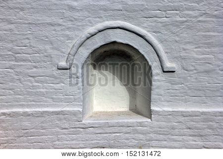 old white stone wall with a niche in the form of a bricked up arched window