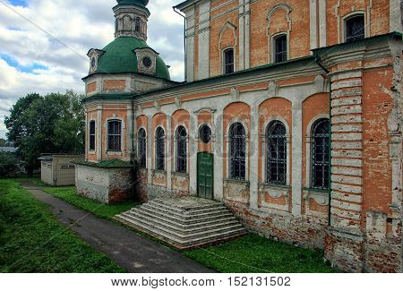 beautiful front of Russian Orthodox Church with the orange brick walls on the background of blue sky with clouds