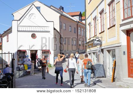 Visby, Sweden - May 12, 2016: The Wallers place (Wallers plats) location in downtown Visby with peopele walking the narrow streets.
