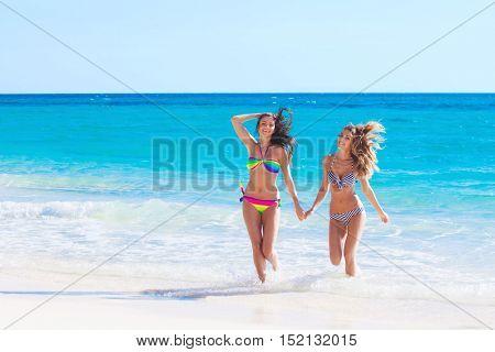 Happy smiling female friends in bikini on vacation