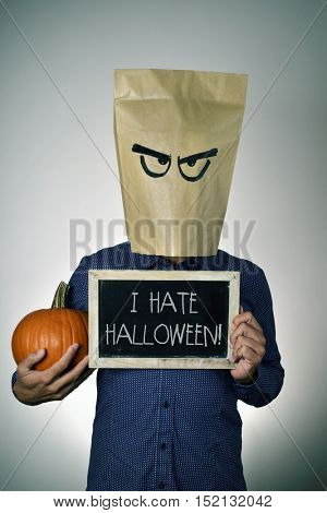 a young man with a paper bag in his head with a funny face, holds a pumpkin in his hand and shows a chalkboard with the text I hate Halloween written in it