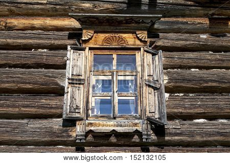 Old window with open shutters glass with a blue sky on the background of the wooden wall of the countryside log house.