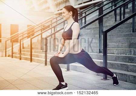 Keep yourself motivated. Delighted young athletic girl doing her exercises while preparing for training and warming up.