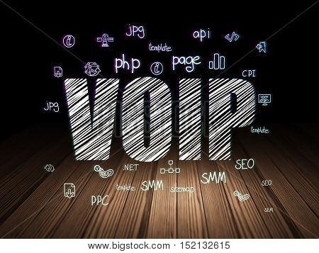 Web development concept: Glowing text VOIP,  Hand Drawn Site Development Icons in grunge dark room with Wooden Floor, black background