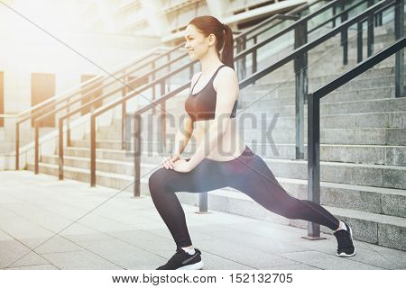 Joyful exercise. Beautiful young woman smiling and stretching her legs while exercising in an urban environment.