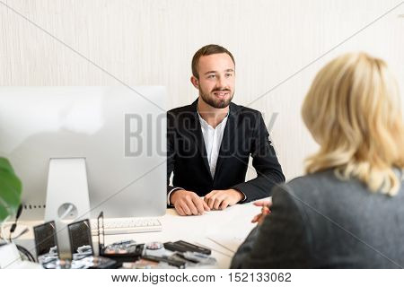 Businesswoman is buying cosmetology at the office. She is sitting at desk and talking with salesman. Man is smiling