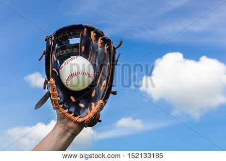 Female hand holding baseball in glove with blue sky