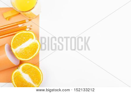 Top view of white desktop with orange halves supplies and copy space