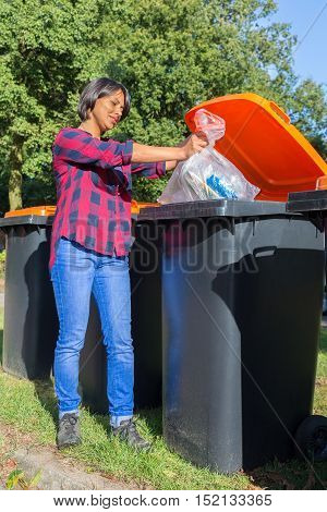 Standing european woman dropping plastic waste in container