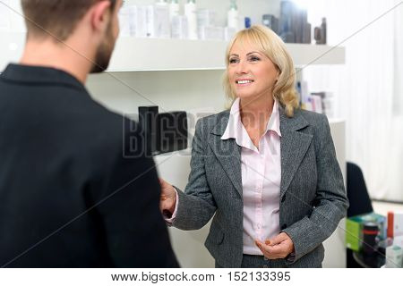 Happy senior businesswoman is buying cosmetics at beauty salon. She is talking with consultant and smiling