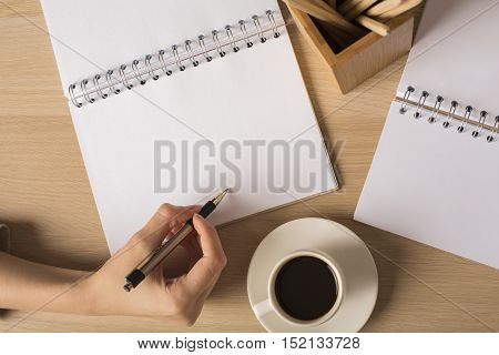Top view of lady's hand writing in blank spiral notepad placed on wooden desktop with pencils and coffee cup. Mock up