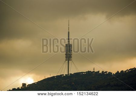 Telecommunications tower in stormy sky in summer