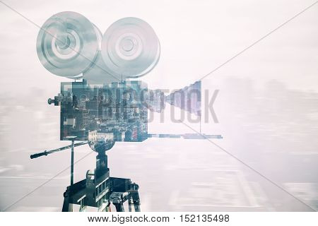 Retro movie camera on abstract city background. Side view. Double exposure. Cinema concept