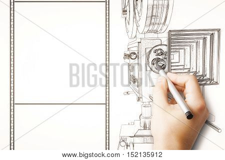 Male hand drawing old style movie camera and blank film strip. Mock up