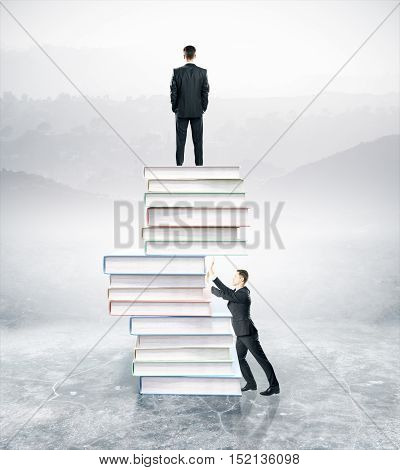 Businesspeople standing on and pushing abstract pile of book on landscape background. Competition concept