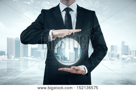 Businessperson holding abstract sphere with city. Close up.