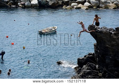 Manarola Italy - September 4 2016: Unidentified woman jumping from high rock to sea in Manarola city in Liguria Italy. One of five Cinque Terre cities (unesco world heritage). Unidentified people visible.