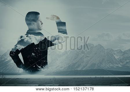 Side view of young businessman looking into the distance on landscape background. Research concept. Double exposure