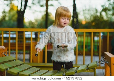 Close up portrait of cute girl playing xylophone outdoor.