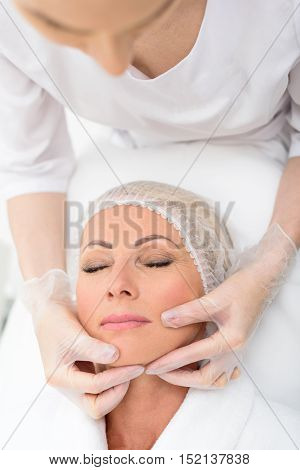 Calm senior woman is getting facial skincare treatment at beauty salon. Beautician is touching her face and checking skin with concentration