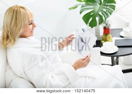 Relaxed senior woman is relaxing on vacation. She is reading magazine and smiling. Woman is sitting in white bathrobe